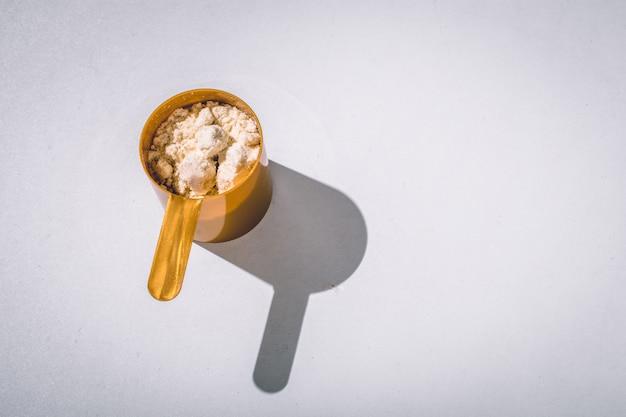 Pelles remplies de poudres de protéines et de vanille. espace de copie. lumière du soleil