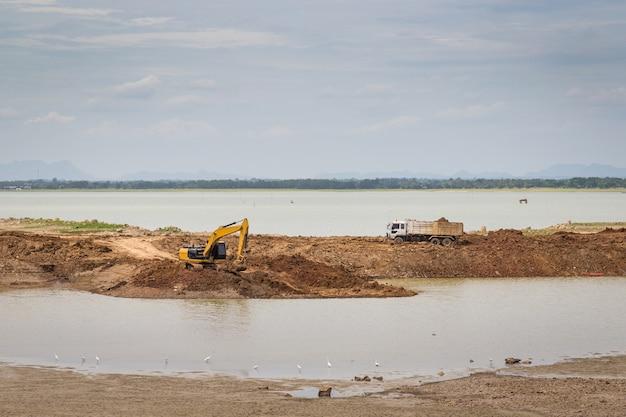 Les pelles rétrocaveuses (excavatrices) et les camions dans le secteur de la construction avec la rivière et le ciel comme toile de fond.