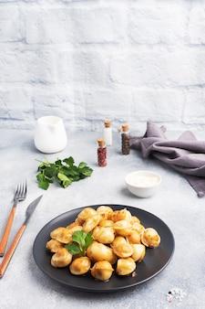 Pelmeni frits traditionnels, raviolis, boulettes farcies de viande sur plaque noire, cuisine russe. table en béton gris, copiez l'espace.