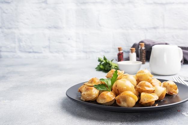 Pelmeni frits traditionnels, raviolis, boulettes remplies de viande sur plaque noire, cuisine russe. table en béton gris, copiez l'espace.