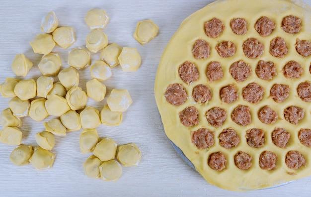 Pelmeni ukrainiens russes non cuits sur planche à découper et ingrédients pour pelmeni maison sur tableau blanc.
