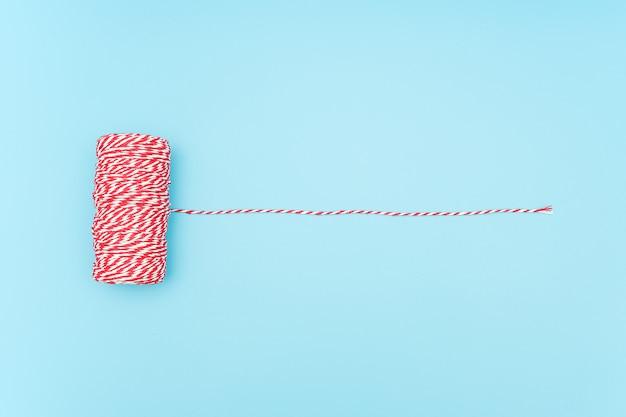 Pelote de ficelle rouge et blanche pour l'emballage de cadeaux de noël, de noël, de boîtes, de colis sur fond bleu.
