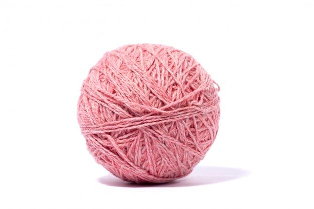 Pelote de fil rose en laine isolé sur mur blanc.