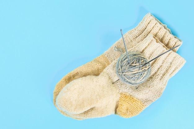 Une pelote de laine avec des aiguilles à tricoter et des chaussettes tricotées sur une table de couleur pastel. couture