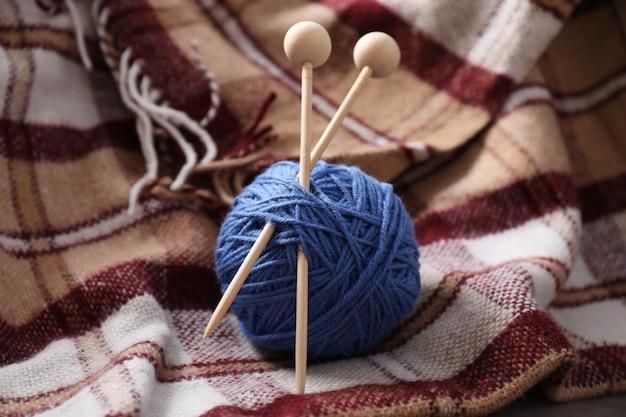 Pelote de laine avec aiguilles à tricoter sur plaid à carreaux