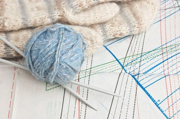Pelote de laine et mitaines sur un motif de fond