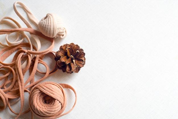 Pelotes de laine et cône sur fond de table en bois