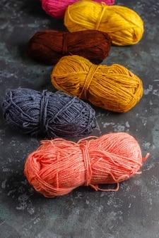 Pelotes de laine de différentes couleurs avec aiguilles à tricoter.