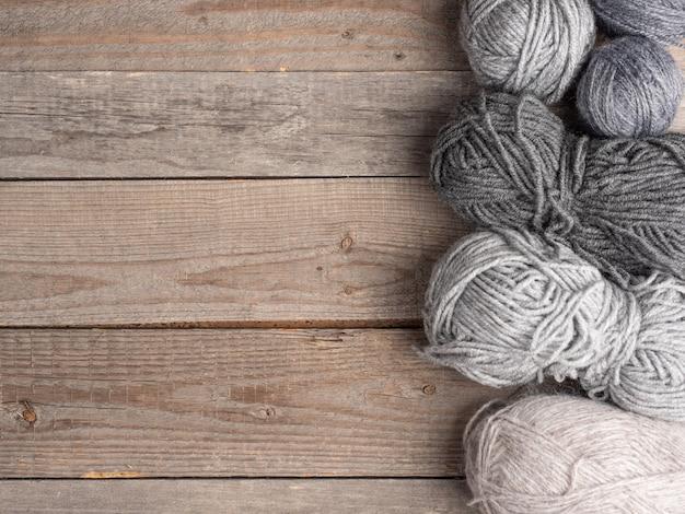 Des pelotes de laine de différentes couleurs et tailles reposent sur une surface en bois naturel. vue de dessus. copiez l'espace.