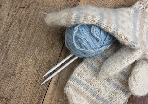 Pelotes de laine et mitaines sur fond de bois
