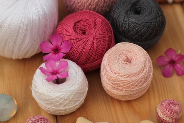 Pelotes de laine roses, blanches et grises.