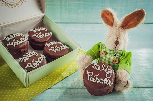 Peluche lapin avec biscuit au miel enrobé de chocolat écrit happy easter dans un coffret cadeau - pao de mel