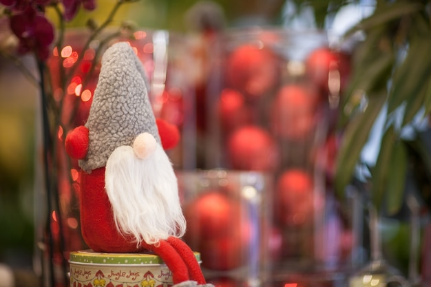 Peluche de noël père noël sur une boîte avec un cadeau sur fond de boules rouges