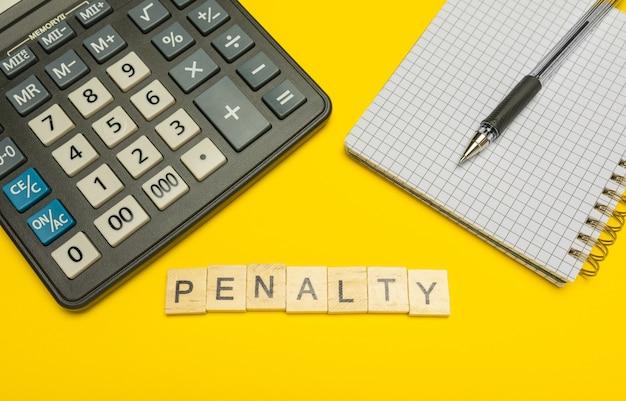 Pénalité de mot faite avec des lettres en bois sur une calculatrice jaune et moderne avec un stylo et un ordinateur portable.