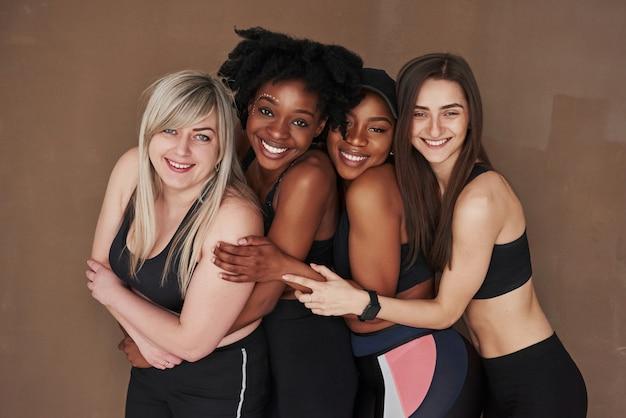 Penché devant eux. groupe de femmes multiethniques debout contre l'espace brun