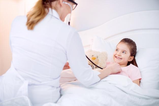 Pendant le diagnostic. femme médecin audition joyeuse fille énergique avec stéthoscope alors qu'elle allongée sur le lit et embrassant l'ours en peluche