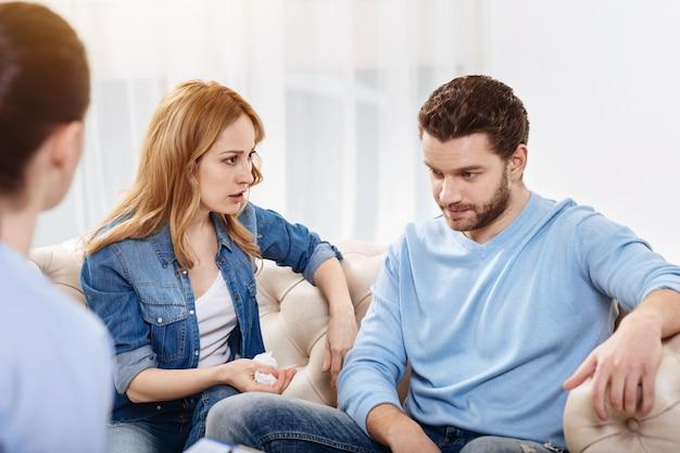 Pendant la séance psychologique. agréable femme séduisante joyeuse regardant son mari et lui dire quelque chose tout en tenant un mouchoir