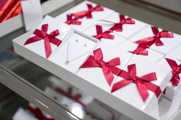 Le pendentif et la boucle d'oreille dans la boîte en papier avec un nœud rouge sont exposés à la vente dans la bijouterie de mode.
