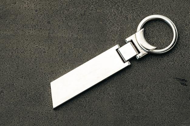 Pendentif clé en métal sur fond de béton foncé close up