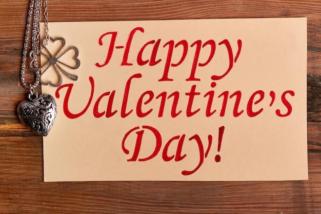 Pendentif en forme de coeur et carte de voeux. bonne inscription de la saint-valentin. bijoux comme cadeau pour chérie.