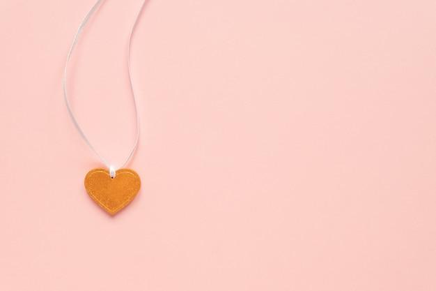 Pendentif en forme de coeur doré sur un ruban blanc sur fond rose. concept de fête de la saint-valentin avec espace de copie. vue de dessus.