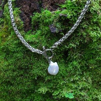 Pendentif perle baroque avec chaîne en argent sur fond de mousse verte