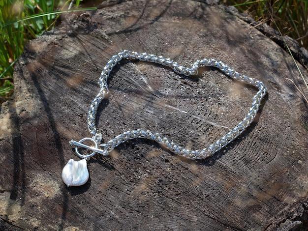 Pendentif perle baroque avec chaîne en argent sur souche d'arbre marron
