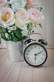 Pendule vintage noire et vase de bouquet de roses
