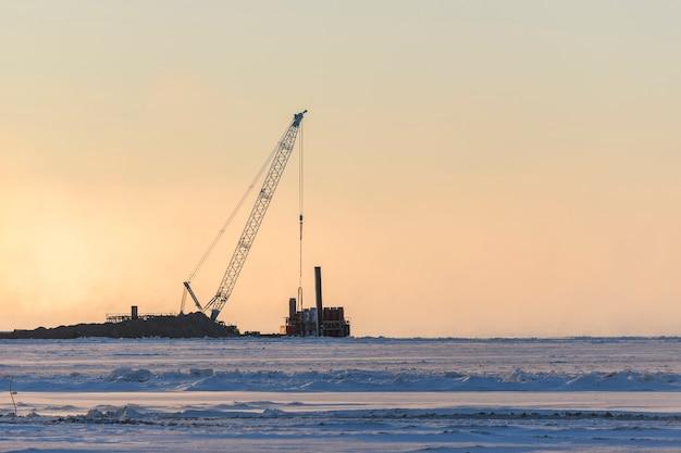 Péniche avec grue. dragueur travaillant en mer. coucher de soleil en mer arctique. travaux maritimes de construction offshore. construction de barrage, grue, barge, drague.
