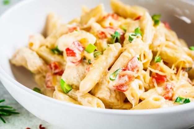 Penne au poulet, poivrons et oignons verts à la sauce crémeuse dans une assiette blanche, fond gris.