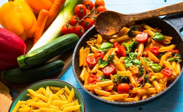 Penne italienne à la sauce tomate et différents types de légumes sur un fond en bois