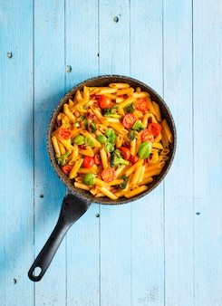 Penne italienne à la sauce tomate et différents types de légumes, sur une table en bois
