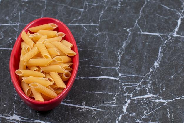 Penne de pâtes crues non cuites dans un bol.