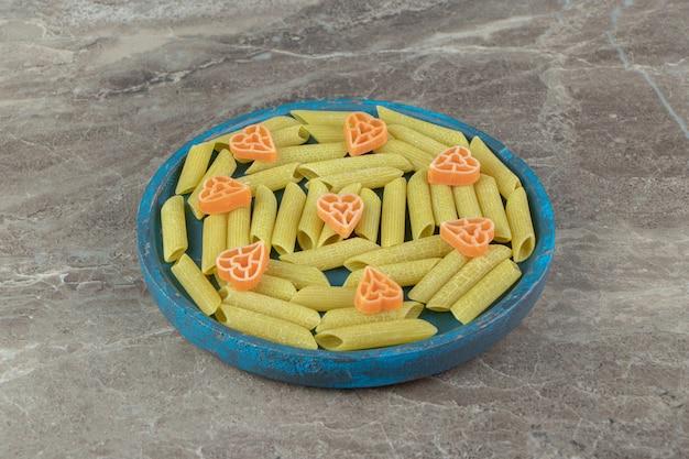 Penne verte et pâtes en forme de coeur sur plaque bleue