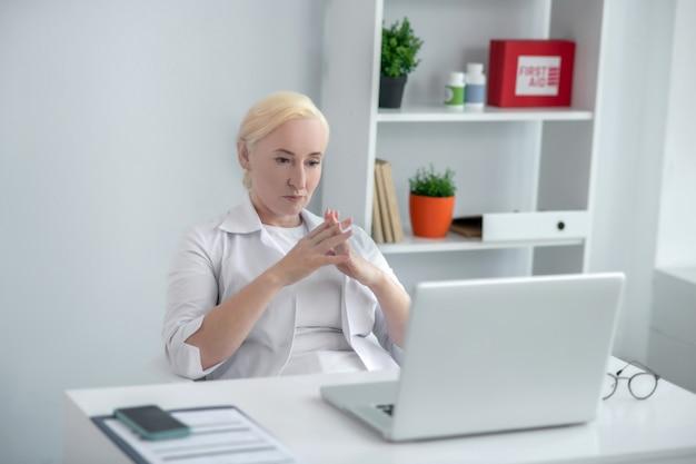 En pensant. blonde médecin d'âge moyen assis à son bureau et à la recherche attentionnée