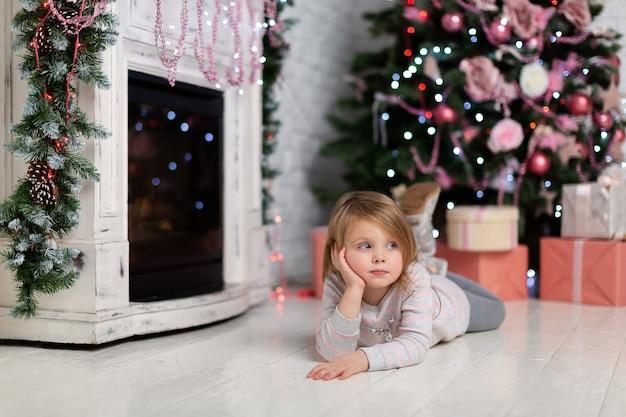 En pensant, la jolie petite fille touche son visage avec une expression réfléchie dessus, en regardant un tas de cadeaux colorés. portrait d'une petite fille pensive rêvant d'un bon cadeau pour la nouvelle année.