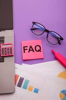Pense-bête avec mot faq sur table rose. concept de questions fréquemment posées. image verticale.