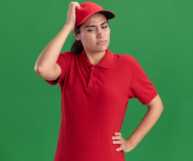 Pensée regardant vers le bas jeune livreuse portant l'uniforme et la tête de grattage casquette isolé sur mur vert
