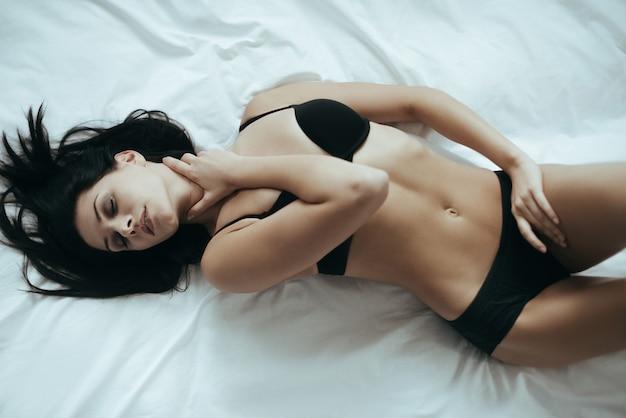 Pensées passionnantes. vue de dessus de la jolie jeune femme en lingerie noire posant de manière séduisante