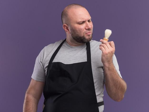 Penser un barbier masculin d'âge moyen en uniforme tenant et regardant un blaireau isolé sur un mur violet