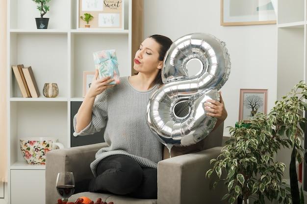 Penser la belle fille le jour de la femme heureuse tenant le ballon numéro huit et regardant le présent dans sa main assise sur un fauteuil dans le salon
