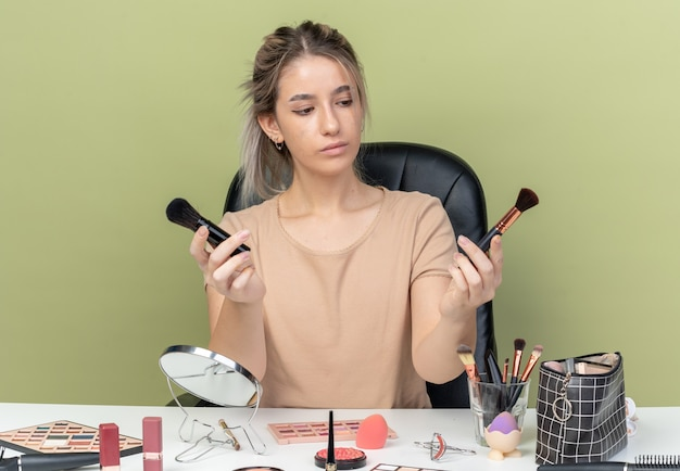 Penser la belle jeune fille assise au bureau avec des outils de maquillage tenant et regardant un pinceau de maquillage isolé sur fond vert olive