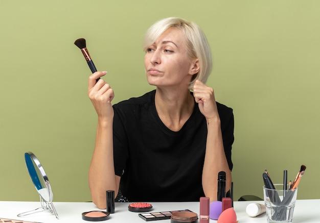 Penser une belle jeune fille assise à table avec des outils de maquillage tenant et regardant un pinceau à poudre isolé sur fond vert olive