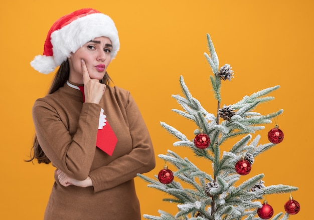 Penser la belle jeune fille portant un chapeau de noël avec une cravate debout à proximité d'un arbre de noël mettant le doigt sur la joue isolé sur un mur orange