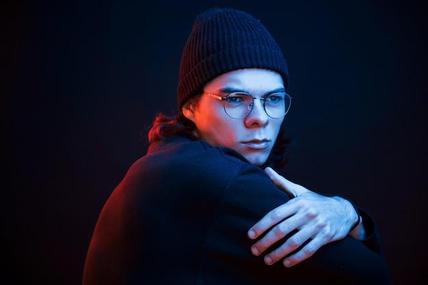 Penser à certains problèmes. studio tourné en studio sombre avec néon. portrait d'homme sérieux