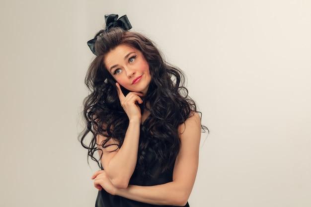 Penser, écouter. portrait de belle jeune femme sur mur gris. modèle féminin brunette mignon caucasien avec de longs cheveux bouclés. concept de beauté, mode, cosmétiques. copyspace pour l'annonce.