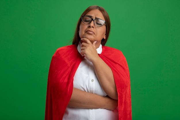 Penser la femme de super-héros d'âge moyen regardant vers le bas portant des lunettes a saisi le menton isolé sur fond vert