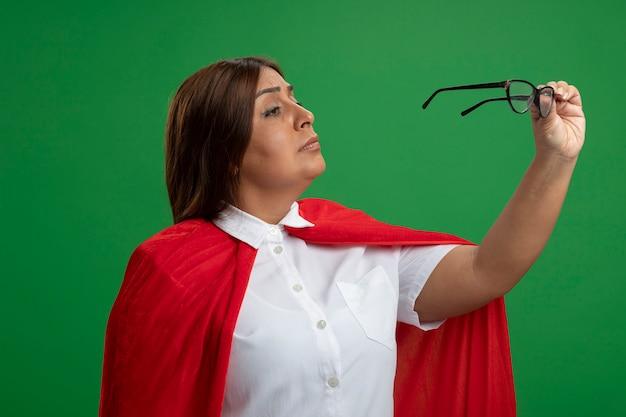 Penser les femmes de super-héros d'âge moyen tenant et regardant des verres isolés sur fond vert