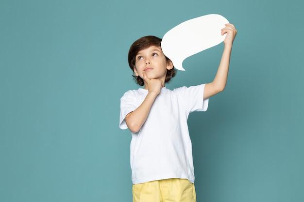 Penser garçon adorable doux mignon en t-shirt blanc tenant une pancarte blanche sur le mur bleu