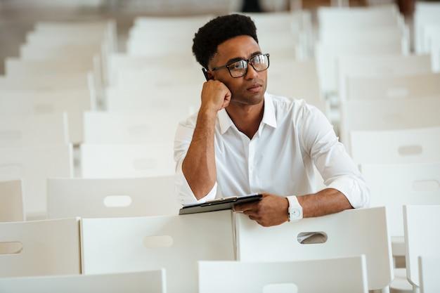 Penser l'homme africain assis coworking avec presse-papiers